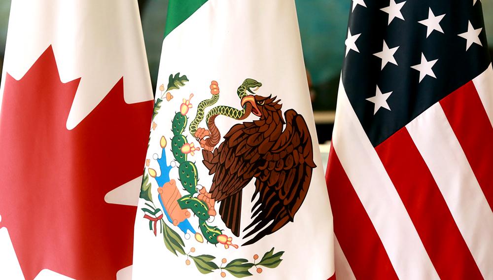Vista parcial de las banderas de Canadá, México y Estados Unidos.