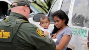 A Honduran woman, holding her 1-year-old child, surrenders to U.S. Border Patrol agents Monday near McAllen, Tex. (David J. Phillip/AP)