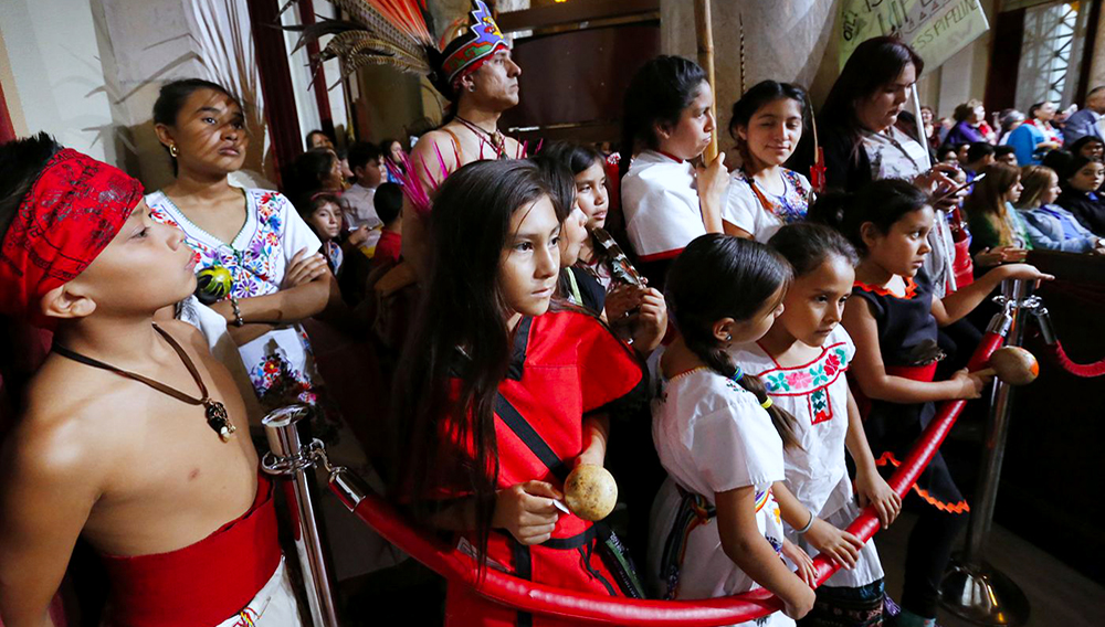 Children listen as L.A. Councilman Mitch O'Farrell, who is a member of the Wyandotte Native American Tribe makes an appeal to the Los Angeles City council meeting celebrating Native American Heritage Month at City Hall on Friday as L.A. officials are weighing a proposal to replace Columbus Day in the city of Los Angeles with Indigenous People's Day. (Al Seib / Los Angeles Times)