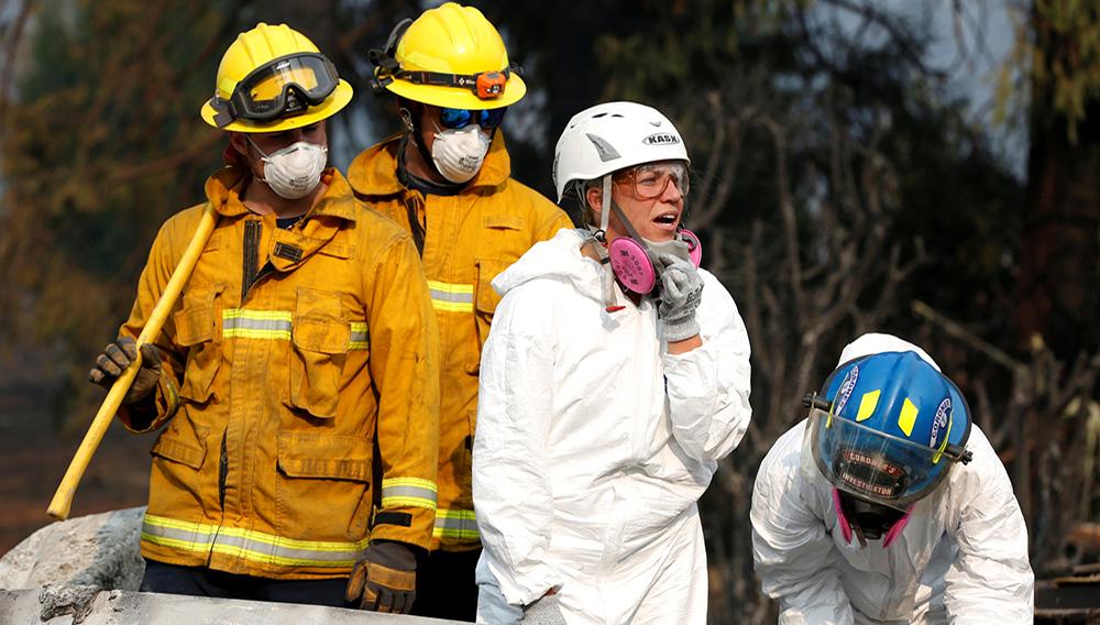 Las antropólogas forenses Kyra Stull (al centro) y Tatiana Vlemincq (derecha) inspeccionando entre los restos de una casa rodante destruida por el Camp Fire en Paradise, California, EEUU. 17 de noviembre de 2018. REUTERS/Terray Sylvester