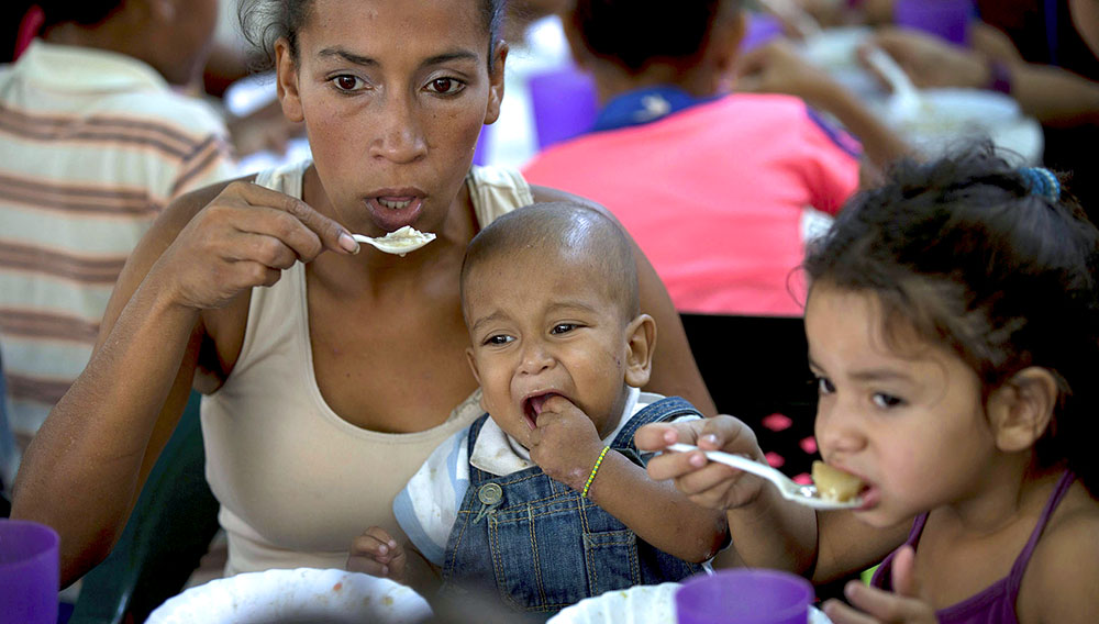 In this Dec. 12, 2017 photo, a mother with her son eat a free meal at a soup kitchen sponsored by the opposition in Caracas, Venezuela. The opposition's outreach is in some ways taking a page from the same socialist leaders they have been struggling for years to unseat from power. (AP Photo/Fernando Llano)