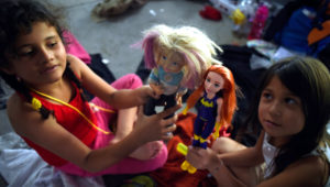 Niñas centroamericanas que avanzan en una caravana que se dirige a Estados Unidos juegan a las muñecas en un albergue temporal en Irapuato, en el estado de Guanajuato, México, el 11 de noviembre de 2018. AFP / Alfredo ESTRELLA