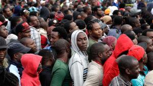 En esta imagen del 3 de octubre de 2016, haitianos se forman en una agencia migratoria en Tijuana, México, con la esperanza de obtener una cita para cruzar hacia el lado estadounidense de la frontera. La Oficina de Aduanas y Protección Fronteriza, solo puede procesar a unas 75 personas al día en San Ysidro, y las autoridades de Tijuana están en descontento con el gran número de personas que están reunidas en el lado mexicano del cruce fronterizo. (AP Foto/Gregory Bull)
