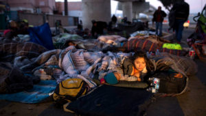 Early morning light illuminates the face of a migrant woman and her child as she wakes after sleeping under a bridge at the Chaparral border crossing in Tijuana, Mexico, Friday, Nov. 23, 2018. The mayor of Tijuana has declared a humanitarian crisis in his border city and says that he has asked the United Nations for aid to deal with the approximately 5,000 Central American migrants who have arrived in the city. (AP Photo/Rodrigo Abd) (AP)