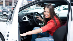 Joven mujer con blusa roja sentada en un coche. iStock Photo