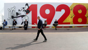 A visitor walks past a mural depicting Disney character Mickey Mouse to celebrate his 90th birthday during the annual MIPCOM television programme market in Cannes, France, October 15, 2018. REUTERS/Eric Gaillard