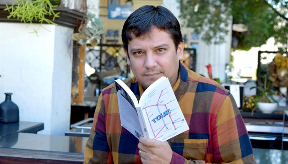 """El escritor peruano Pedro Medina León posa con un ejemplar de su libro """"Tour"""" en Miami (EE.UU.). EFE"""
