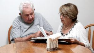 Un anciano que está al cuidado de una mujer también adulta que está revisando un libro.