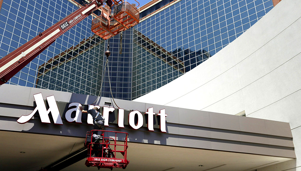 Un hombre trabaja en un letrero de la cadena de hoteles Marriott en Little Rock, Arkansas, el 30 de abril de 2013. (AP Foto/Danny Johnston, File)