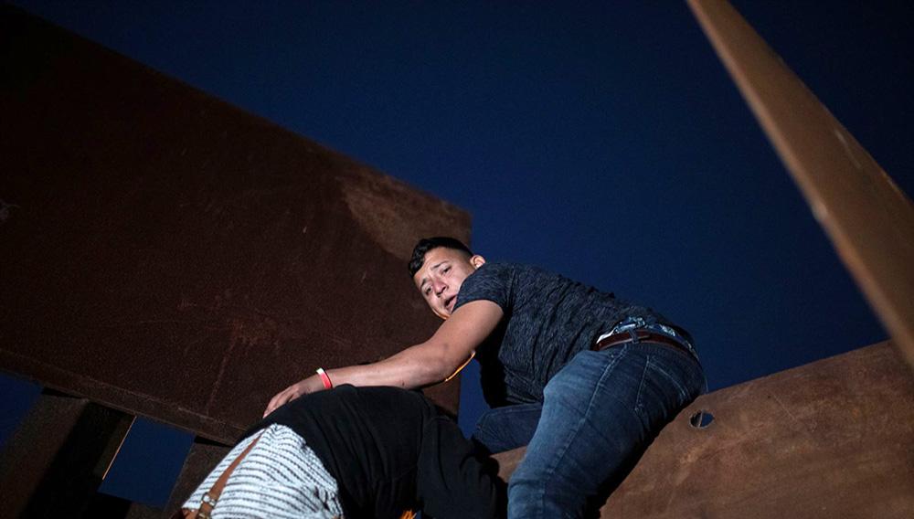 Migrantes, parte de una caravana de miles de centroamericanos que tratan de entrar ilegalmente a EE.UU., escalando una valla fronteriza desde Tijuana, México. Diciembre 3 de 2018. Foto: Voz de América.