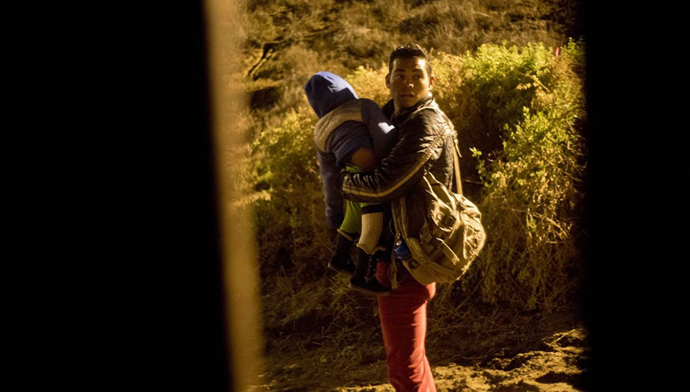 Un migrante hondureño camina con su hijo en brazos en territorio de Estados Unidos tras saltar la valla fronteriza que separa a San Diego, California, de Tijuana, México, el jueves 29 de noviembre de 2018. (AP Foto/Ramón Espinosa)