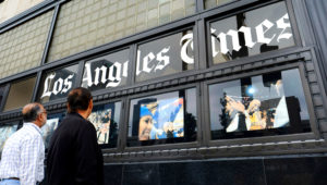 In this May 16, 2016, file photo, pedestrians look at news photos posted outside the Los Angeles Times building in downtown Los Angeles. The Los Angeles Times suspended the head of its Beijing bureau Wednesday, May 16, 2018, after he was accused of sexual misconduct for a second time. (AP Photo/Richard Vogel, File)