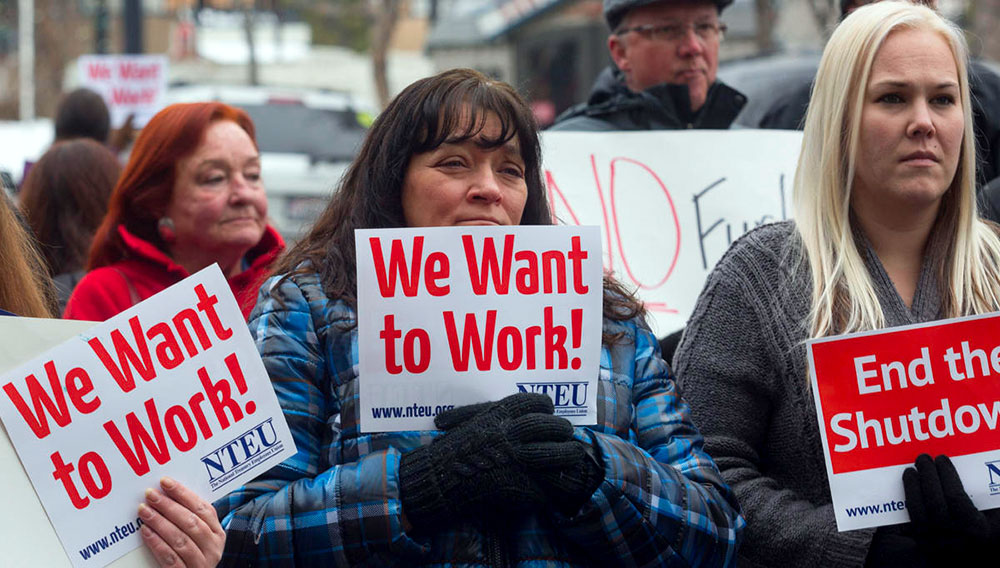IRS employee Donna Orton (C) holds a sign protesting the government shutdown on January 10, 2019 in Ogden, Utah. None of these workers received their wages on January 11. Natalie Behring, Getty Images, AFP