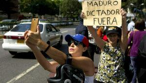 Una miembro de la oposición se toma una selfie junto a una mujer sosteniendo un cartel durante una protesta en Caracas, Venezuela, el viernes 11 de enero de 2019. (AP Foto/Fernando Llano)