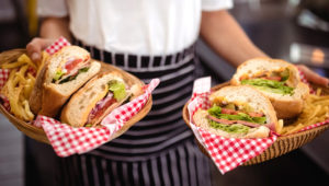 Torso de camarera con comidas frescas en cestas de mimbre. istockphoto.com