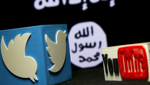 A 3D plastic representation of the Twitter and Youtube logo is seen in front of a Daesh flag. Photo: Sputnik International