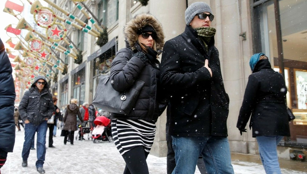 Nicole and Lee Richard, of Buffalo, N.Y., look cool in their sunglasses walking along State Street by Macy's Department Store in Chicago on Sunday. — Chuck Berman / Chicago Tribune, Dec. 8, 2013
