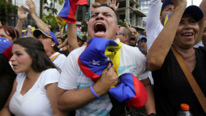 Anti-government protesters cheer as Juan Guaido, head of Venezuela's opposition-run congress, declares hi interim president of the South American country until a new election can be called, at a rally demanding the resignation of President Nicolas Maduro in Caracas, Venezuela. (AP Photo/Boris Vergara)