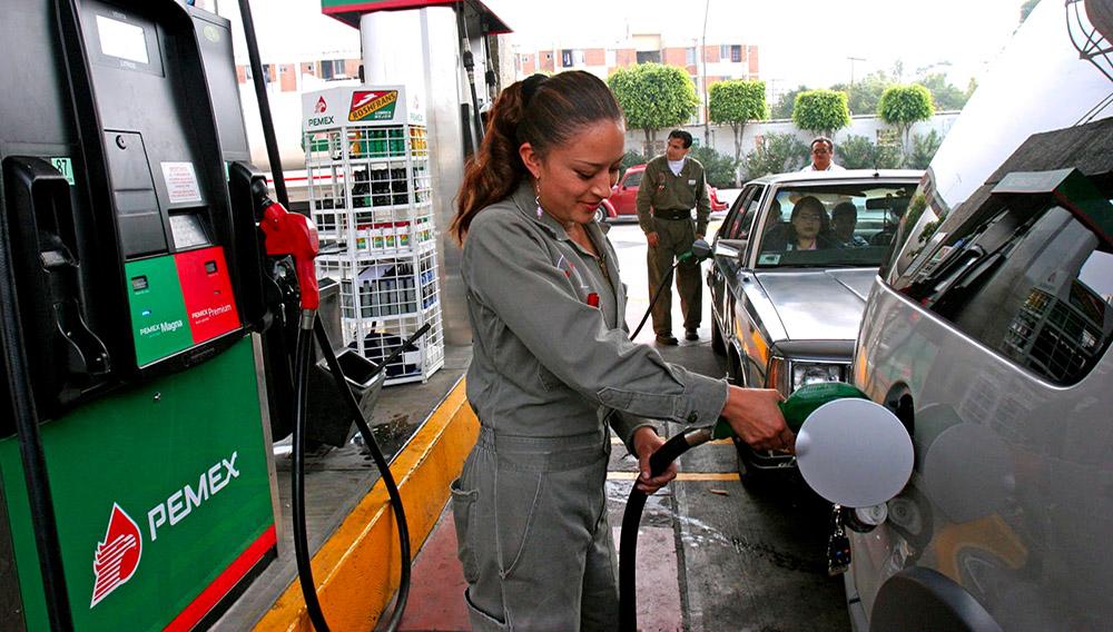 Trabajadora de una gasolinera atendiendo a un automovilista en México.