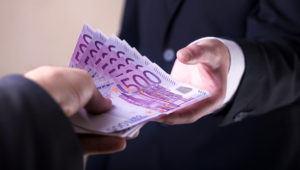 Man in Men's Suits.Bribe and corruption with euro banknotes. Shutterstock