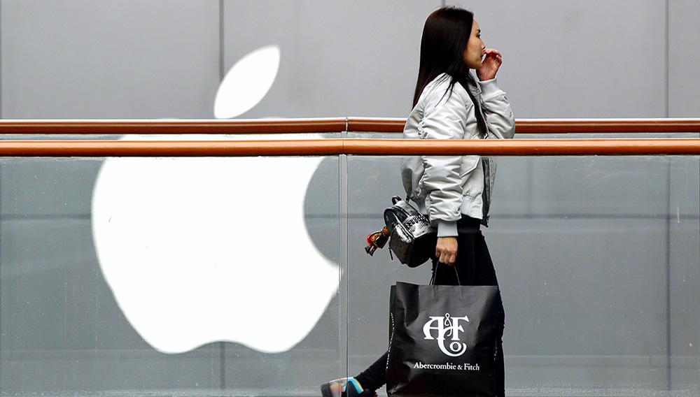 Una mujer con una bolsa de la cadena de tiendas de moda estadounidense Abercrombie & Fitch pasa por delante de una tienda de Apple en un centro comercial de Beijing, en China, el 26 de febrero de 2019. (AP Foto/Andy Wong)
