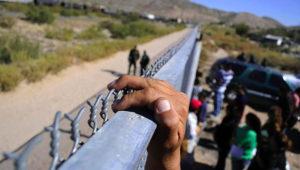 Mano en primer plano de un inmigrante que está agarrado de la parte superior de una valla de seguridad en la frontera Estados Unidos-México. Foto: Internet.