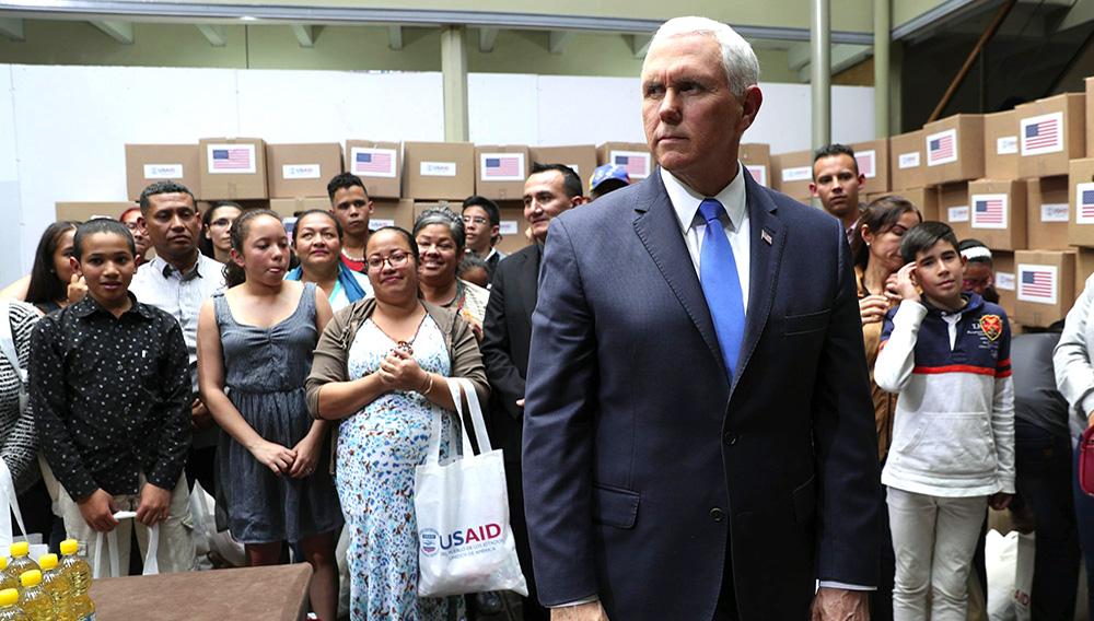 El vicepresidente estadounidense Mike Pence está de pie en un cuarto lleno de ayuda humanitaria destinada a Venezuela antes de una reunión con un grupo de migrantes venezolanos en Bogotá, Colombia, el lunes 25 de febrero de 2019. (AP Foto/Martin Mejia)