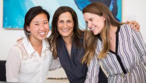 Tres mujeres de distintas edades y razas sonriendo juntas en una oficina | modernwell.co
