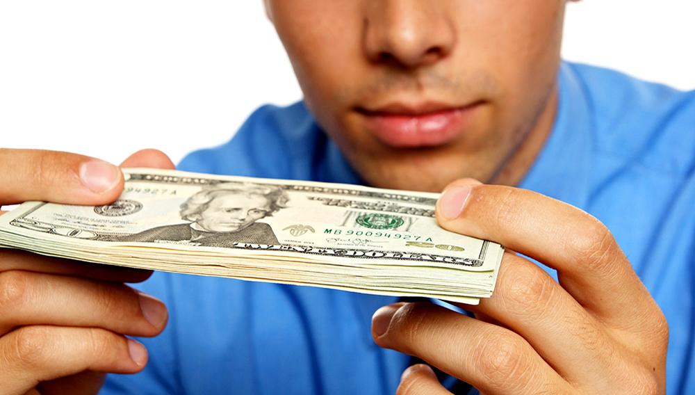 Hombre joven pensativo en camisa azul mirando billetes.   Foto Stock