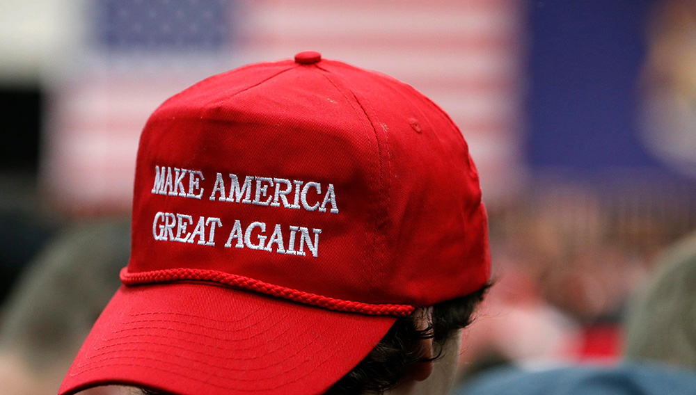 Joven usa la gorra roja de la campaña de Donald Trump con la frase Make America great again. | Internet