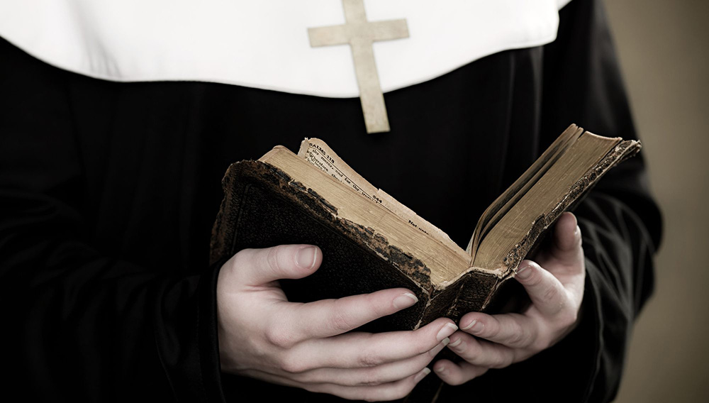 A nun holding a bible. | Getty Images
