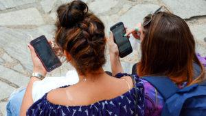 Dos mujeres jóvenes, de espaldas a la cámara, revisan sus teléfonos móviles sentadas en una calle.   Foto: Internet