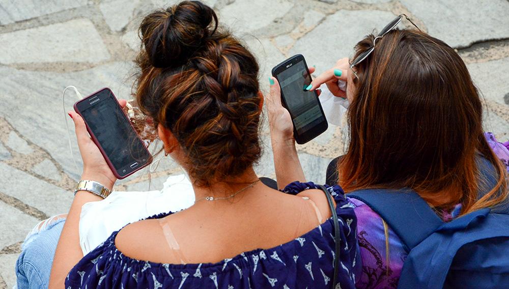 Dos mujeres jóvenes, de espaldas a la cámara, revisan sus teléfonos móviles sentadas en una calle. | Foto: Internet
