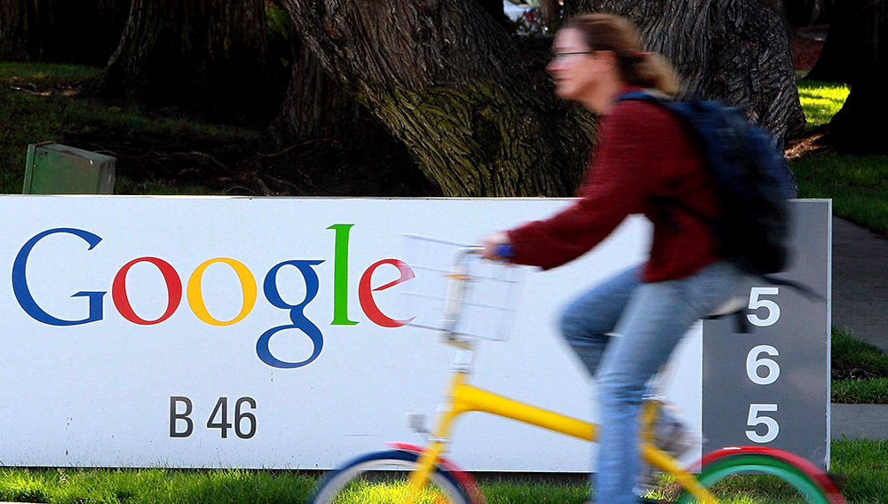 A bicyclist rides by a sign at the Google headquarters in Mountain View, Calif. (Photo: Justin Sullivan, Getty Images)