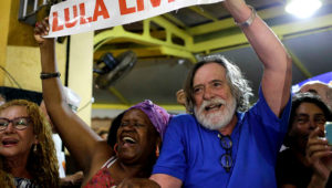 """El actor brasileño Jose de Abreu, derecha, y una mujer sostienen un cartel con la leyenda """"Lula Libre"""" al arribar al bar Amarelinho en Río de Janeiro, Brasil, 8 de marzo de 2019. (AP Foto/Silvia Izquierdo)"""