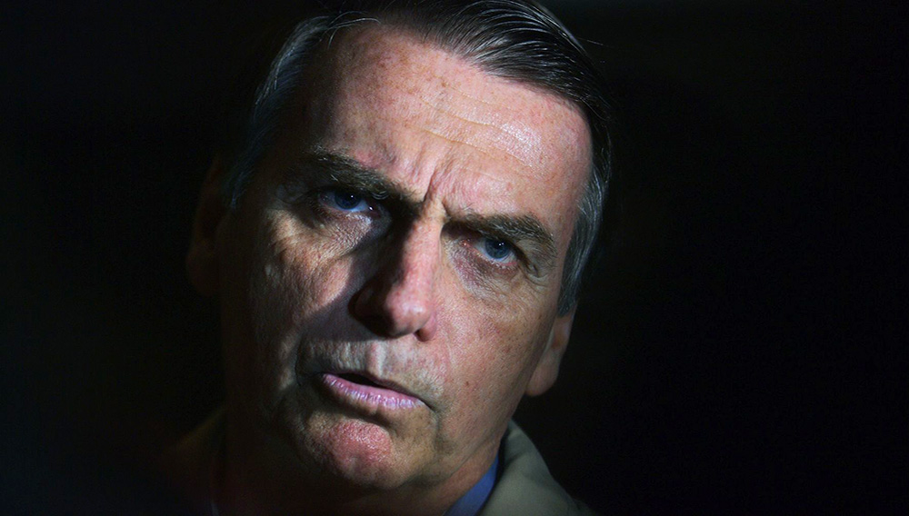 Brazilian far-right presidential candidate Jair Bolsonaro speaks to the press during a visit to the Federal Police station in Rio de Janeiro, Brazil on October 17, 2018. CARL DE SOUZA | AFP | Getty Images