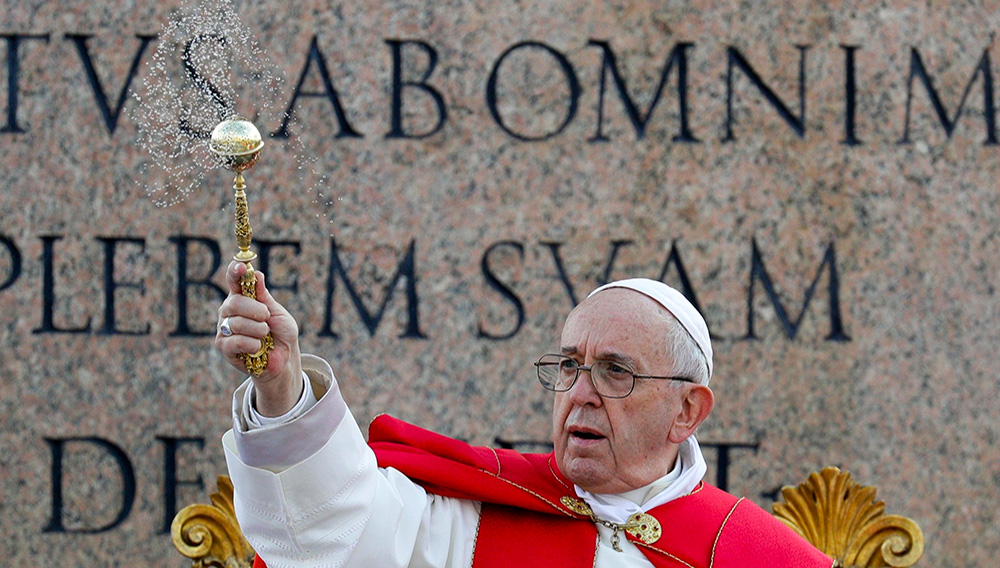 Pope Francis asperses holy water as he celebrates Palm Sunday Mass in St. Peter's Square at the Vatican, Sunday, April 14, 2019. The Roman Catholic Church enters Holy Week, retracing the story of the crucifixion of Jesus and his resurrection three days later on Easter Sunday. (AP Photo/Gregorio Borgia)
