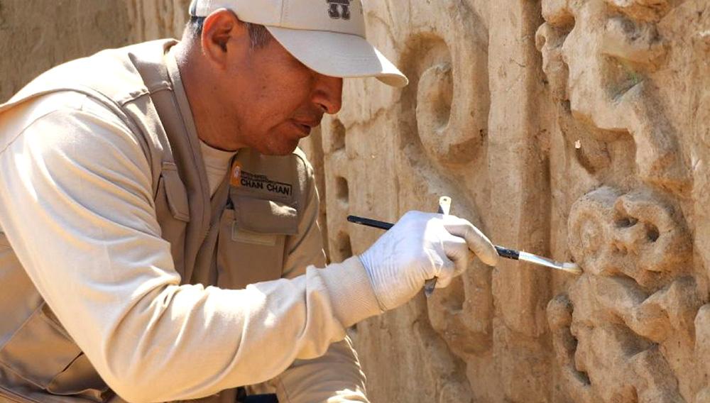 Trabajador limpia la decoración encontrada en un nuevo hallazgo arqueológico dentro del complejo Chan Chan, al norte de Perú.