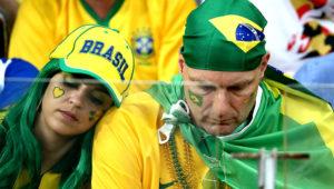 Dos hinchas adultos de la selección de Brasil, hombre y mujer en primer plano, vestidos con los colores verde y amarillo y con la mirada baja.