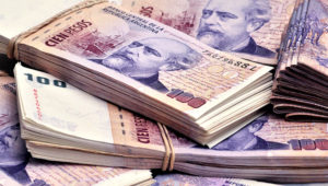 Stacks of 100 Argentine pesos are displayed for a photograph in Buenos Aires, Argentina, on Monday, Dec. 13, 2010.