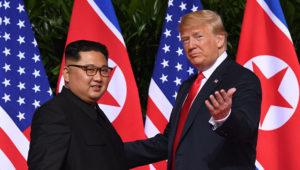 Delante de las banderas de Corea del Norte y Estados Unidos, Donald Trump hace un gesto con la mano izquierda invitando a un sonriente Kim Jong Un a mirar a las cámaras.