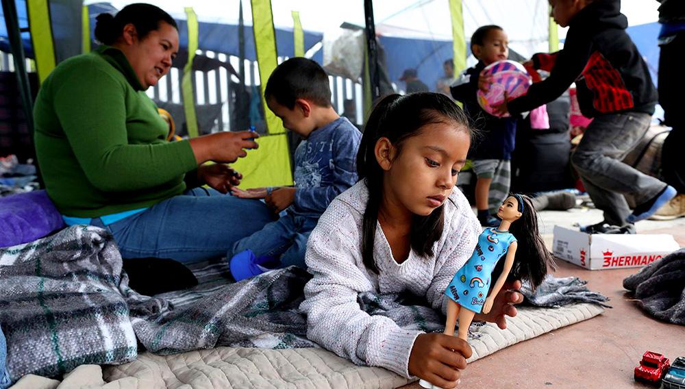Niña migrante de ropa blanca jugando con una muñeca de vestido celeste, atrás otro niño con su madre, a la espera de cruzar la frontera entre México y Estados Unidos, en Tijuana.