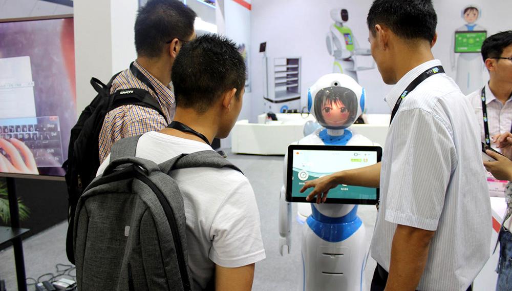 Personas miran la pantalla de un robot de acompañamiento para ancianos presentado en una feria tecnológica de China.