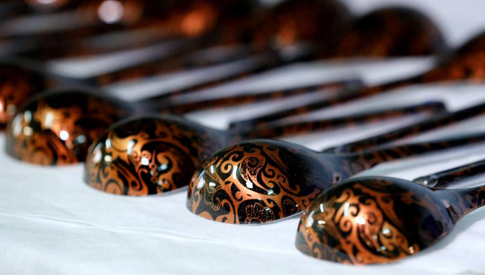 Lozhkas o cucharas rusas, instrumento oficial del Mundial Rusia 2018, recién decoradas y puestas en fila sobre una mesa de color blanco.