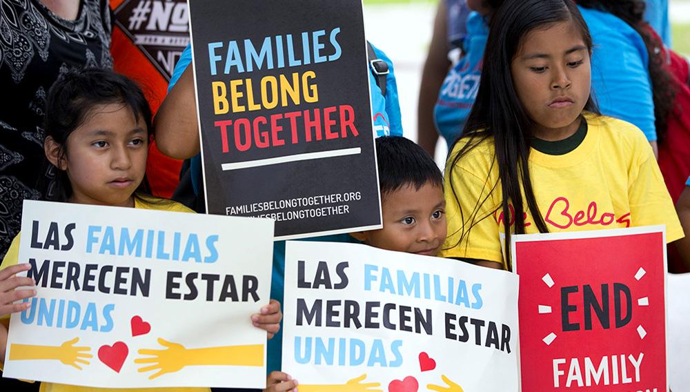 Niños migrantes mostrando carteles en inglés y español en los que piden que las familias tienen que estar unidas.