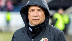 Hernán Darío Gómez, entrenador de la selección de fútbol de Panamá, mirando a la cámara y vistiendo una casaca negra con capucha, que tiene el símbolo de la Federación Panameña de Fútbol, FEPAFUT.
