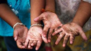 Trabajo infantil, dos niños muestran sus manos abiertas y sucias