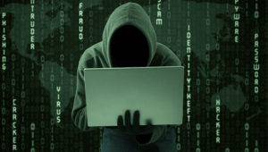 Hacker typing on a laptop with binary code background. Bigstock.