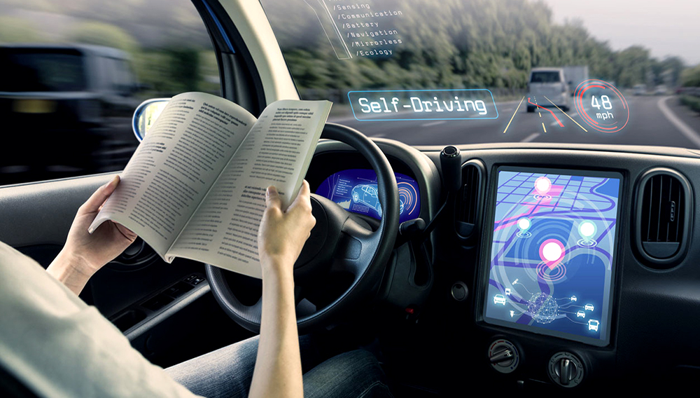 Cockpit of autonomous car. A vehicle running self driving mode and a woman driver reading book. Photo: iStock