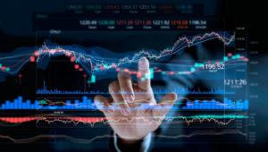 Businessman touching stock market graph on a virtual screen display. Photo: Shutterstock